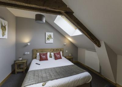 Chambre d'hôtel mansardée avec un lit double